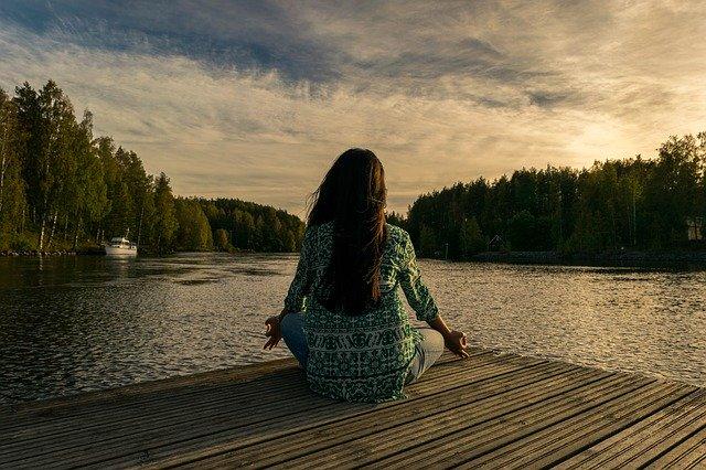 femme qui médite devant un lac